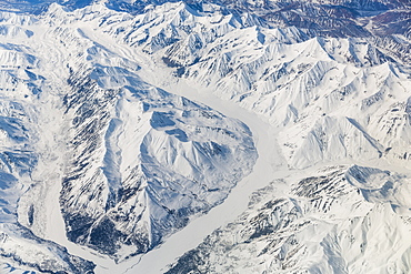Aerial View Of A Glacier Passing Through Snow Covered Mountains In The Alaska Range, Interior Alaska, USA, Winter