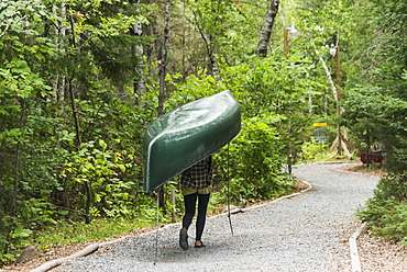 A Young Woman Carrying A Green Canoe On Her Head Down A Trail, Ontario, Canada