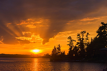 Sunrise Casting An Orange Glow Over The Sky And Reflected In A Tranquil Lake, Ontario, Canada