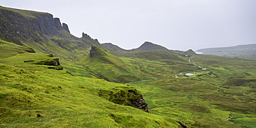Fog Over The Lush Green Landscape With Cliffs And Peaks, Staffin, Scotland