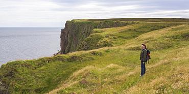 A Woman Stands On Grass Near A Ridge Overlooking Duncansby Head, John O'groats, Scotland