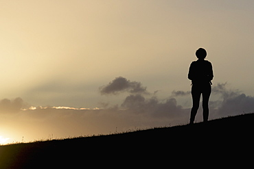 Silhouette Of A Person Standing On A Ridge Overlooking The Sunlight Shining Through The Clouds On Calton Hill, Edinburgh, Scotland