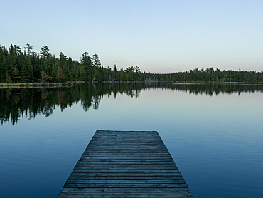 Wooden Dock Leading Out To A Tranquil Lake At Sunrise, Whiteshell, Manitoba, Canada