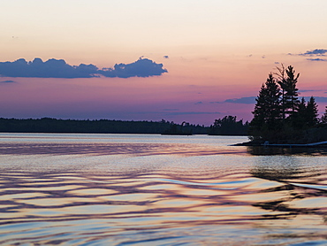 Lake Of The Woods At Sunrise With The Pink Sky Reflected In The Tranquil Water, Ontario, Canada