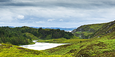 A River Flowing Into A Pond Surrounded By Lush Grass And Forest In The Highlands, Scotland