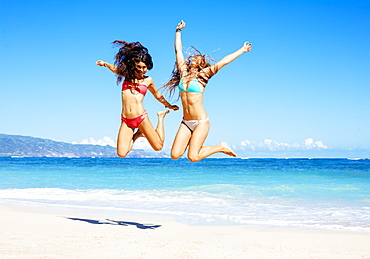 Two Attractive Girls In Bikinis Jumping On The Beach. Best Friends Having Fun, Summer Lifestyle.