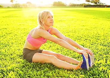 Attractive Fit Young Woman Stretching Before Exercise, Sunrise Early Morning Backlit. Healthy Lifestyle Sports Fitness Concept.