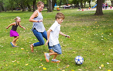 A Mother Playing Soccer With Her Kids In A Park During A Family Outing, Edmonton, Alberta, Canada