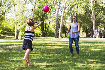 Mother And Daughter Throwing A Ball In A Park During A Family Outing, Edmonton, Alberta, Canada