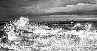Waves Crashing Along The Coast With A Small Lighthouse At The End Of A Pier, Amble, Northumberland, England