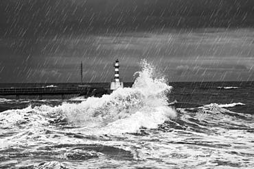 Rainfall And Splashing Waves With A Lighthouse Along The Coast, Amble, Northumberland, England