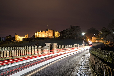 Light Trails On A Road And Illuminated Building In The Background At Nighttime, Alnwick, Northumberland, England
