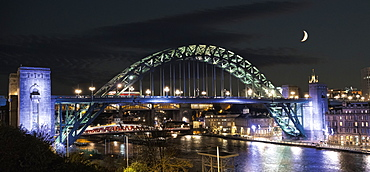 Tyne Bridge Illuminated At Nighttime Over River Tyne With A Crescent Moon In The Sky, Newcastle, Tyne And Wear, England