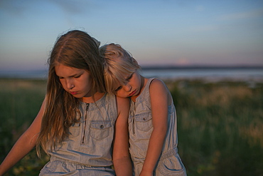 Sisters Sitting Together On The Beach At Sunset, Surrey, British Columbia, Canada