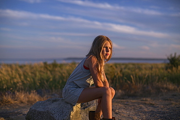 Girl In Contemplation Sitting On A Rock On The Beach At Sunset, Surrey, British Columbia, Canada
