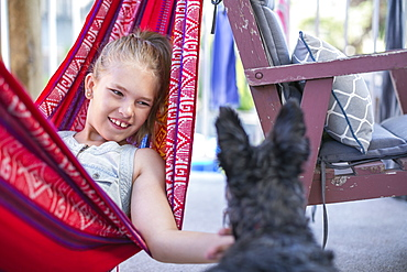 Girl Relaxing In A Hammock And Petting Her Dog, Langley, British Columbia, Canada