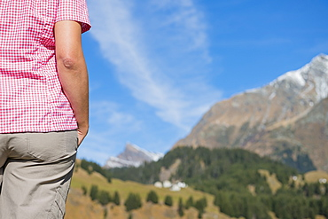 A Woman Stands Looking At The Blue Sky And Swiss Alps, San Bernardino, Grisons, Switzerland