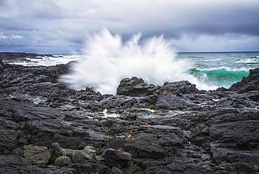 A Wave Splashes Against The Rocks On Iceland's Southern Coast, Iceland