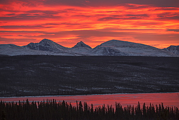 Sunset Over The Rancheria Range Of Mountains And The Ice Covered Swan Lake, Yukon, Canada