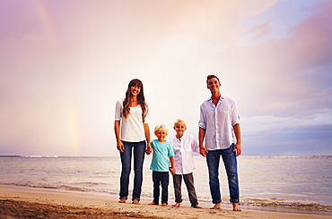 Happy Young Family On The Beach At Sunset With Amazing Rainbow