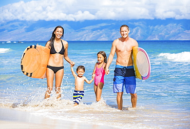 Happy Family With Surfboards On The Beach In Hawaii