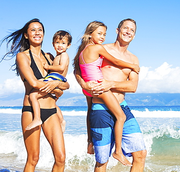 Happy Mixed Race Family Of Four On Tropical Sunny Beach