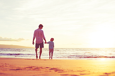 Father And Son Holding Hands Walking Together On The Beach At Sunset