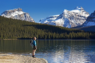 Female Hiker Standing Along A Rocky Shoreline Of A Mountain Lake With Snow Peaked Mountains Reflecting In Lake And Blue Sky, Banff National Park, Alberta, Canada