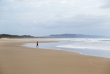 Person Walks Towards The Water On A Beach Along The Noose North Shore Under A Cloudy Sky, Noosa, Queensland, Australia