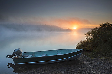 The Sun Rises Through Fog Over The Kvichak River In Autumn With A Skiff In The Foreground, Bristol Bay Region, Southwest Alaska.