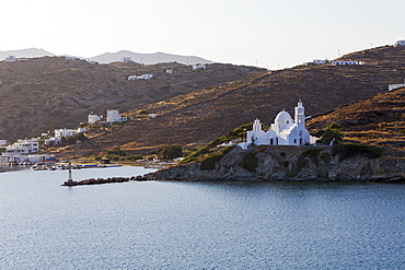 Port And White Church On A Cliff At The Water's Edge, Ios, Greece