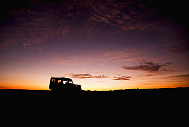 A Truck Parked On The Savannah With It's Headlights On Is Shown In Silhouette On The Horizon At Sunrise, Blue And Orange Sky With A Few Thin Clouds In The Background, Narok, Kenya