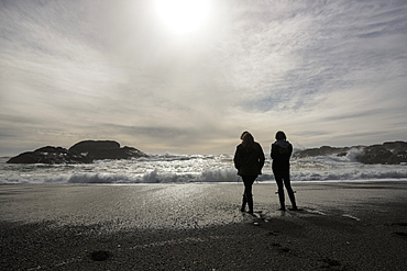 Silhouettes Two Girls Standing At The Water's Edge Looking At The Waves, Vancouver Island, Tofino, British Columbia, Canada