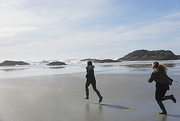 Teenage Girls Running On A Wet Beach At The Coast, Vancouver Island, Tofino, British Columbia, Canada