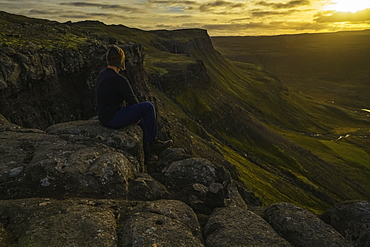 Person Sitting On A Cliff Top Overlooking The Sunset Near The Town Of Djupavik, Iceland