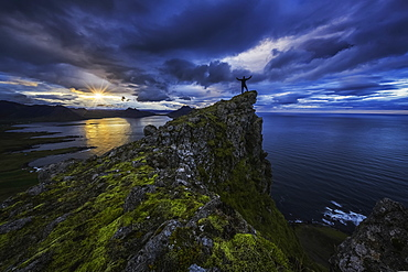 Man Standing On Top Of A Sea Cliff At Sunset Along Iceland's Strandir Coast In The West Fjord Region, Iceland