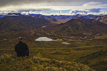 Man Stitting On A Look Out Overlooking The Blackstone Valley, Along The Dempster Highway, Yukon, Canada