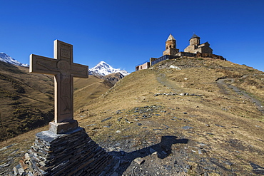 Stone Cross And Gergeti Trinity Church With Mount Kazbek In The Background, Kazbegi, Mtskheta-Mtianeti, Georgia