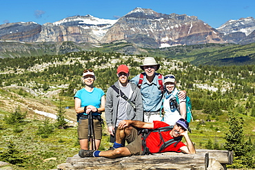 Group Of Hikers Posing On A Log Bench With Valley Below And Mountains And Blue Sky In The Distance, Banff, Alberta, Canada