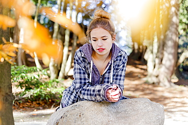 This Young Teenage Girl Hangs Out Alone In A Park, Sitting On A Rock In A Thoughtful Disengaged Position Thinking To Herself, New Westminster, British Columbia, Canada