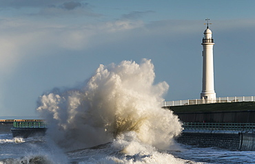 A Large Wave Breaks And Crashes Against The Shore In Front Of A Lighthouse, Sunderland, Tyne And Wear, England