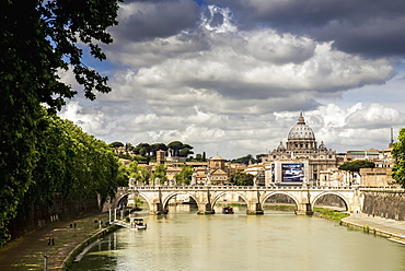 View Of St. Peter's Basilica In The Distance With A Bridge And Modern Car Advertisement Over The Tiber River, Rome, Italy