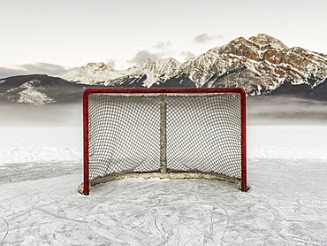 A Hockey Net On Frozen Pyramid Lake With The Rugged Canadian Rockies Mountain Range In The Background, Jasper National Park, Alberta, Canada