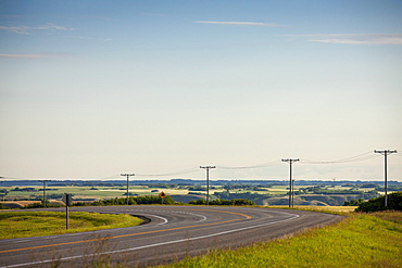 Electrical Wires Along A Curving Road With Farmland In The Distance, Saskatchewan, Canada
