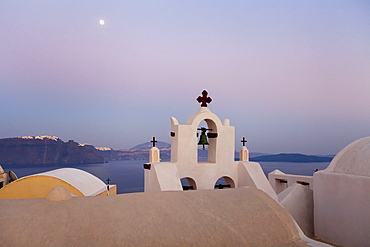 Orthodox Church With Bell And A Moon High In The Sky At Dusk, Oia, Santorini, Greece