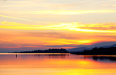 A Dramatic And Colourful Sunset Reflected In Water With Silhouetted Shoreline And Mountains, Kenmore, County Kerry, Ireland