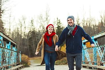A Young Couple Running On A Bridge In A City Park In Autumn, Edmonton, Alberta, Canada