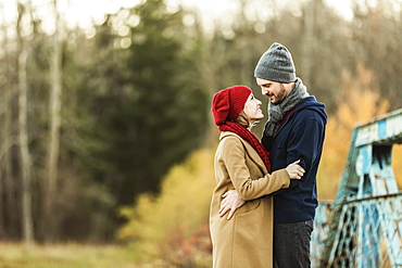 A Young Couple Embracing Each Other And Looking Into Each Other's Eyes On A Bridge In A City Park In Autumn, Edmonton, Alberta, Canada