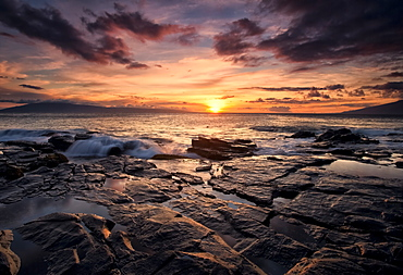 Sunset Over The Ocean With Wet Black Rock Along The Shore, Hawaii, United States Of America