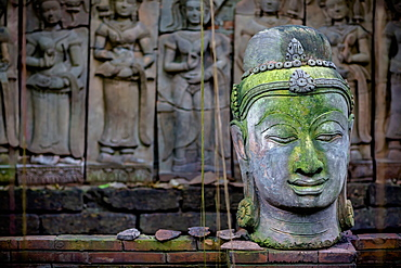 A Terra Cotta Head Of Buddha Sits In Front Of Bas-Relief In A Terra Cotta Garden, Chiang Mai, Thailand